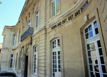 Lawrence Weiner, DOWN AND OUT, OUT AND DOWN, 1971, lettrage adhésif. Photographie Franck Couvreur, vue de la façade de l'hôtel de Caumont.